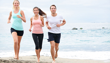 27540018 - running friends on beach jogging group training. exercising runners training outdoors living healthy active lifestyle. multiracial fitness runner people working out together outside smiling happy.