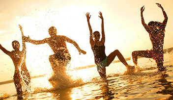 11161454 - group of happy young people dancing at the beach on beautiful summer sunset